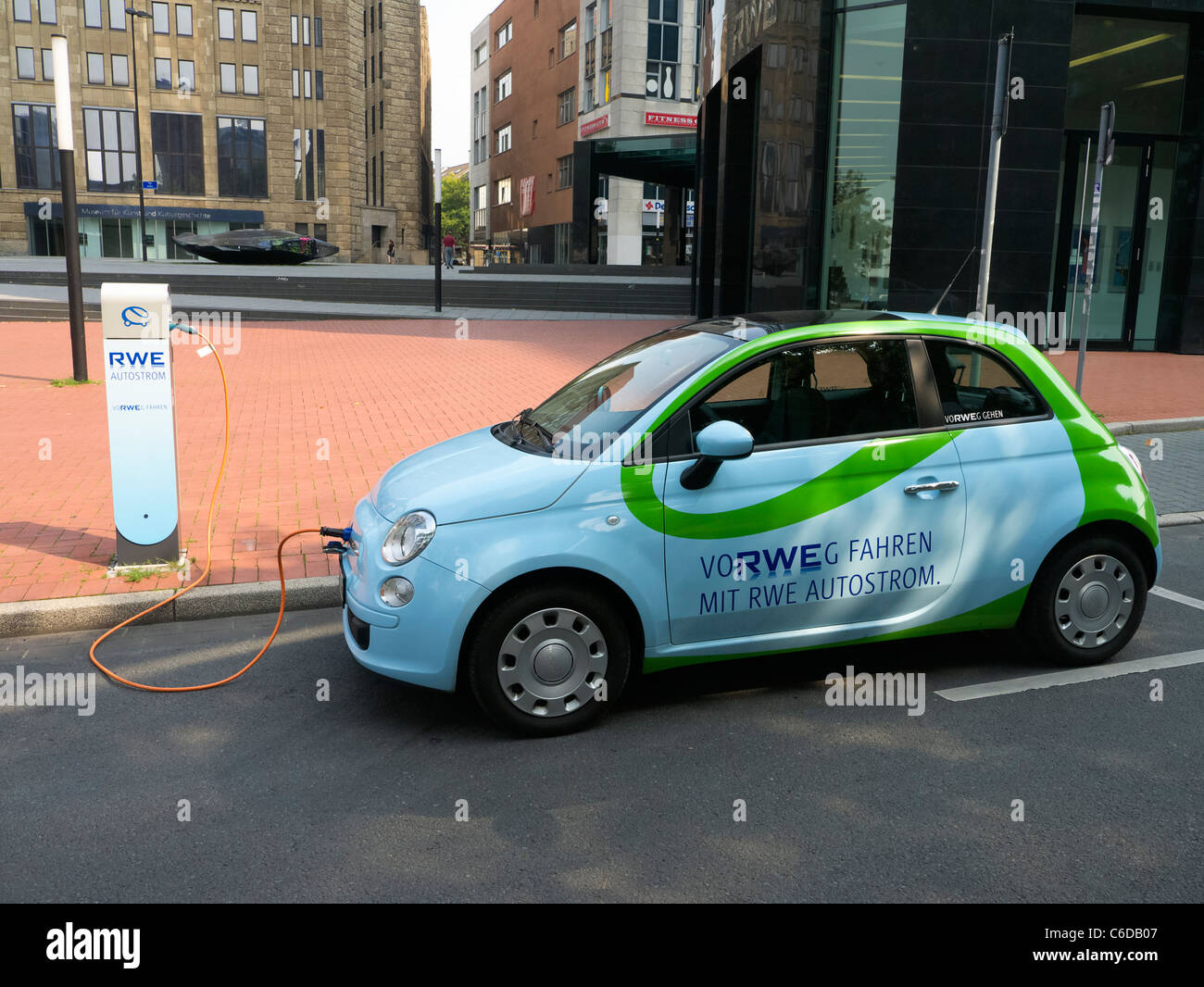 Fiat 500 electric car owned by power company RWE being recharged on street in Dortmund Germany - Stock Image