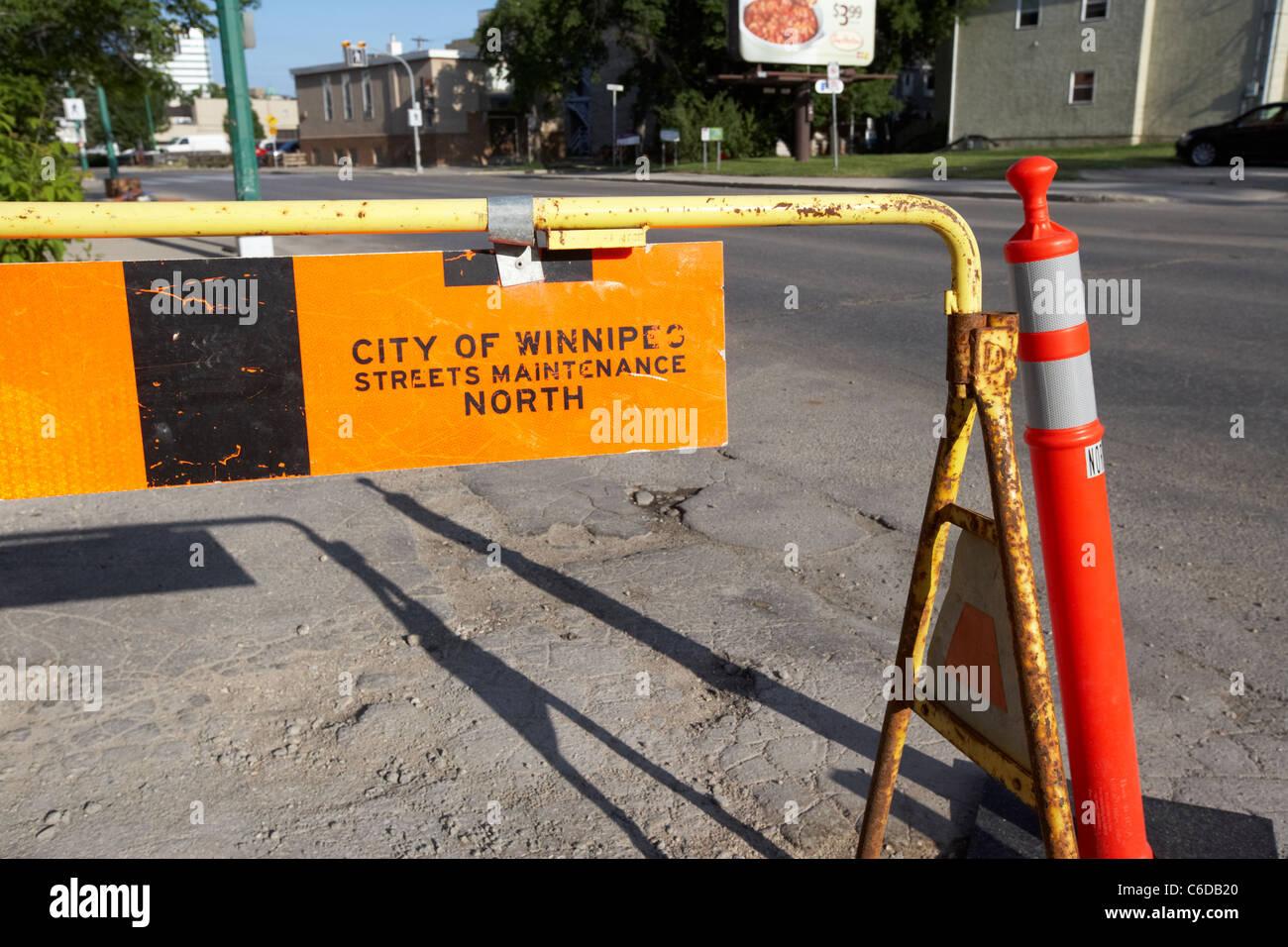 city of winnipeg streets maintenance broken sidewalk road barrier safety manitoba canada - Stock Image