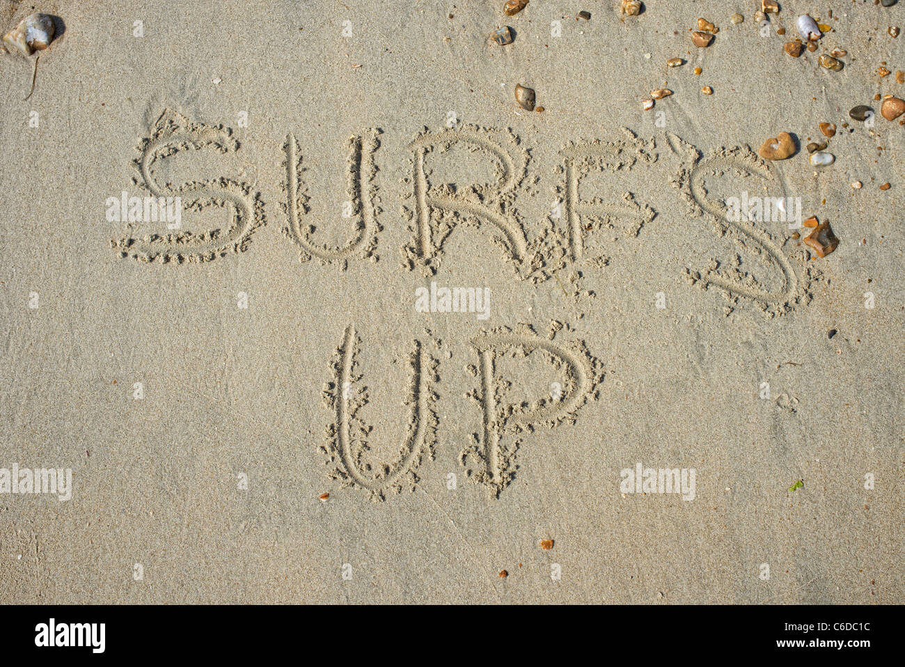 surfs up message written in the sand Stock Photo