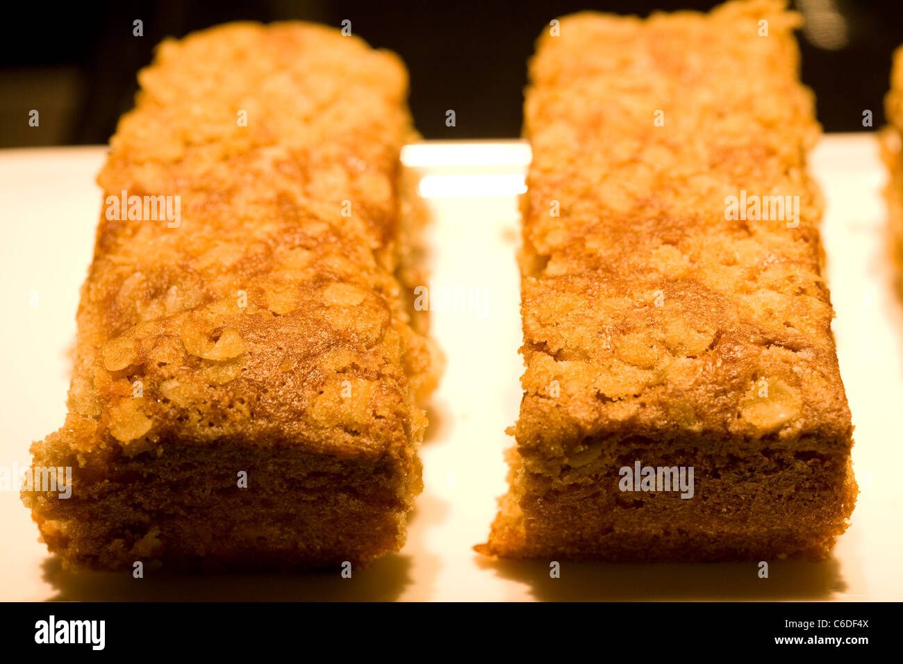 two pieces of cake arranged on a white rectangular plate - Stock Image
