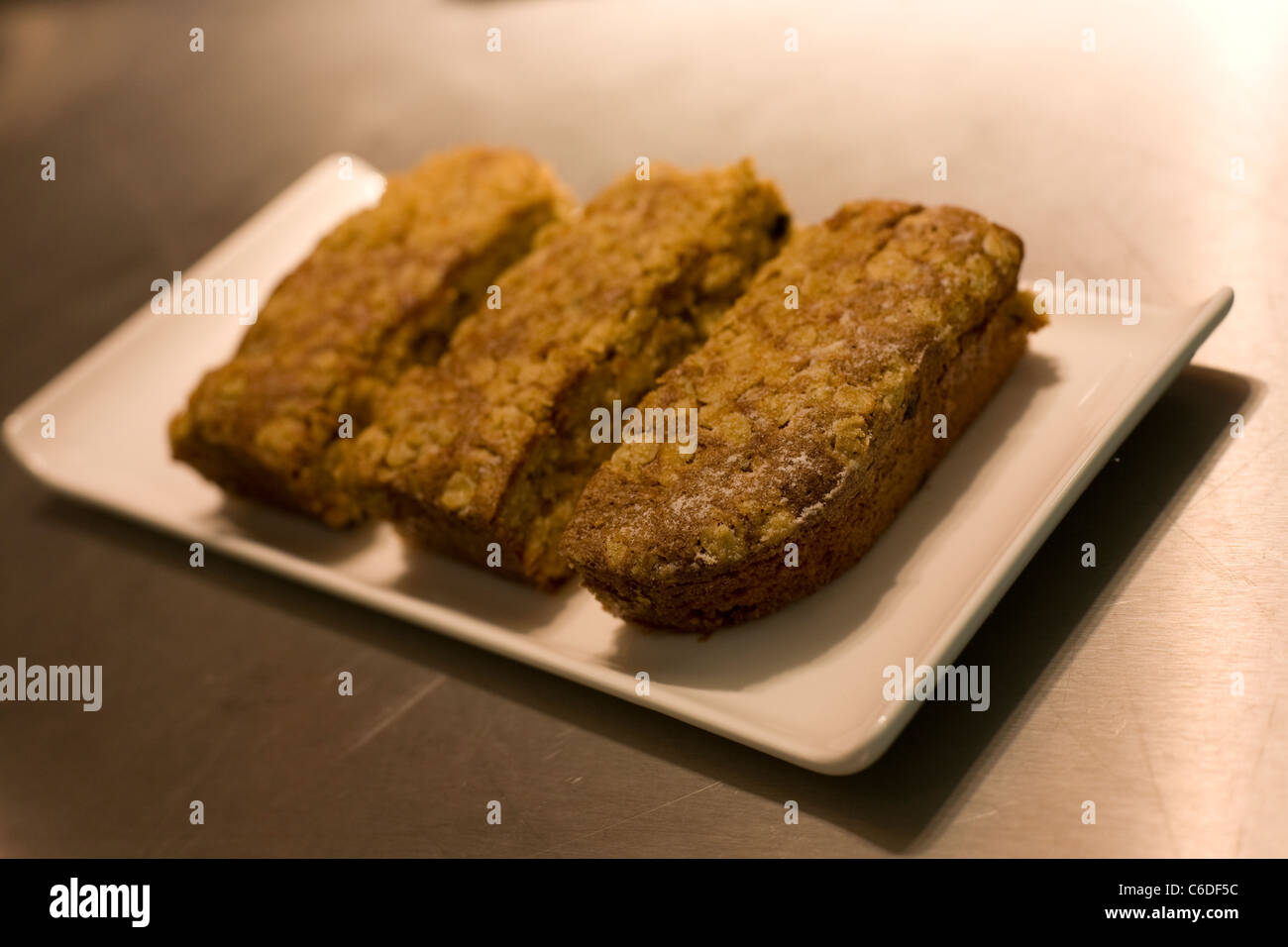 Three pieces of cake arranged on a white rectangular plate - Stock Image
