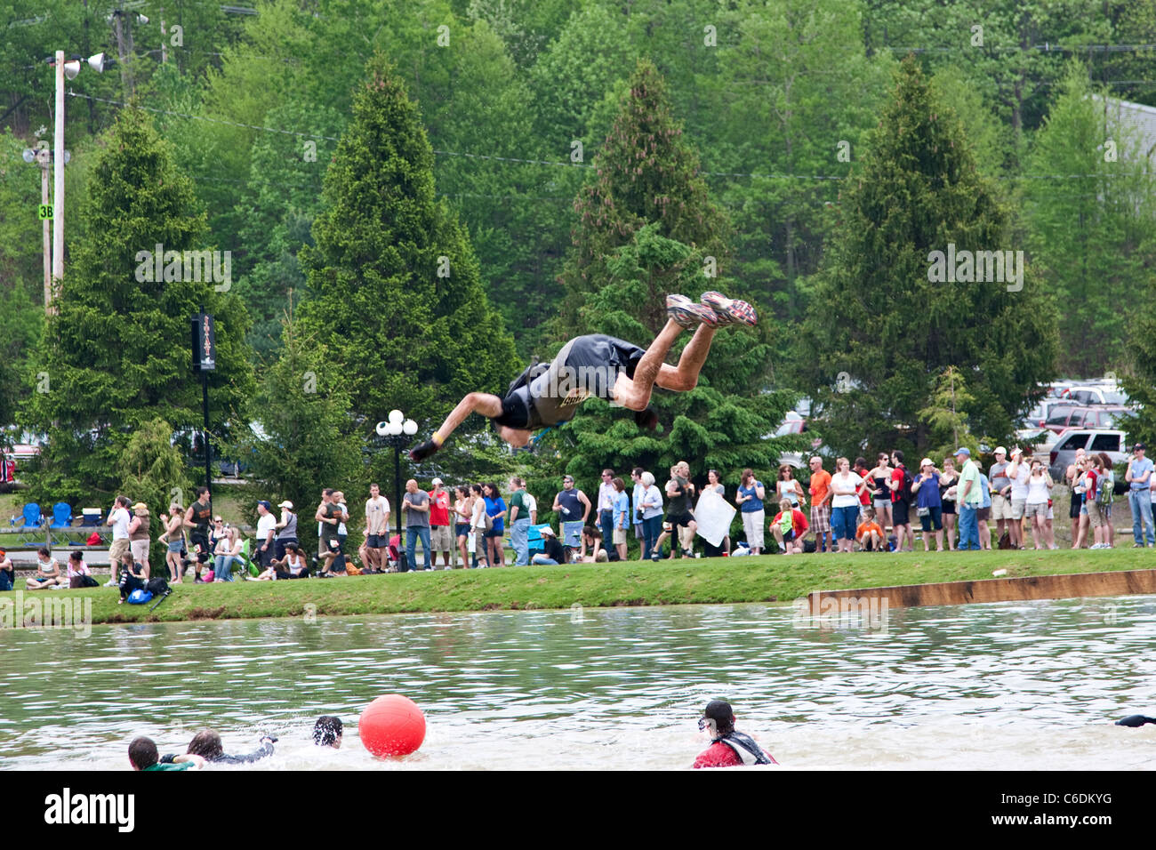A Tough Mudder participant leaps into the water as part of the 'Walk the Plank' section of the course. Tough - Stock Image