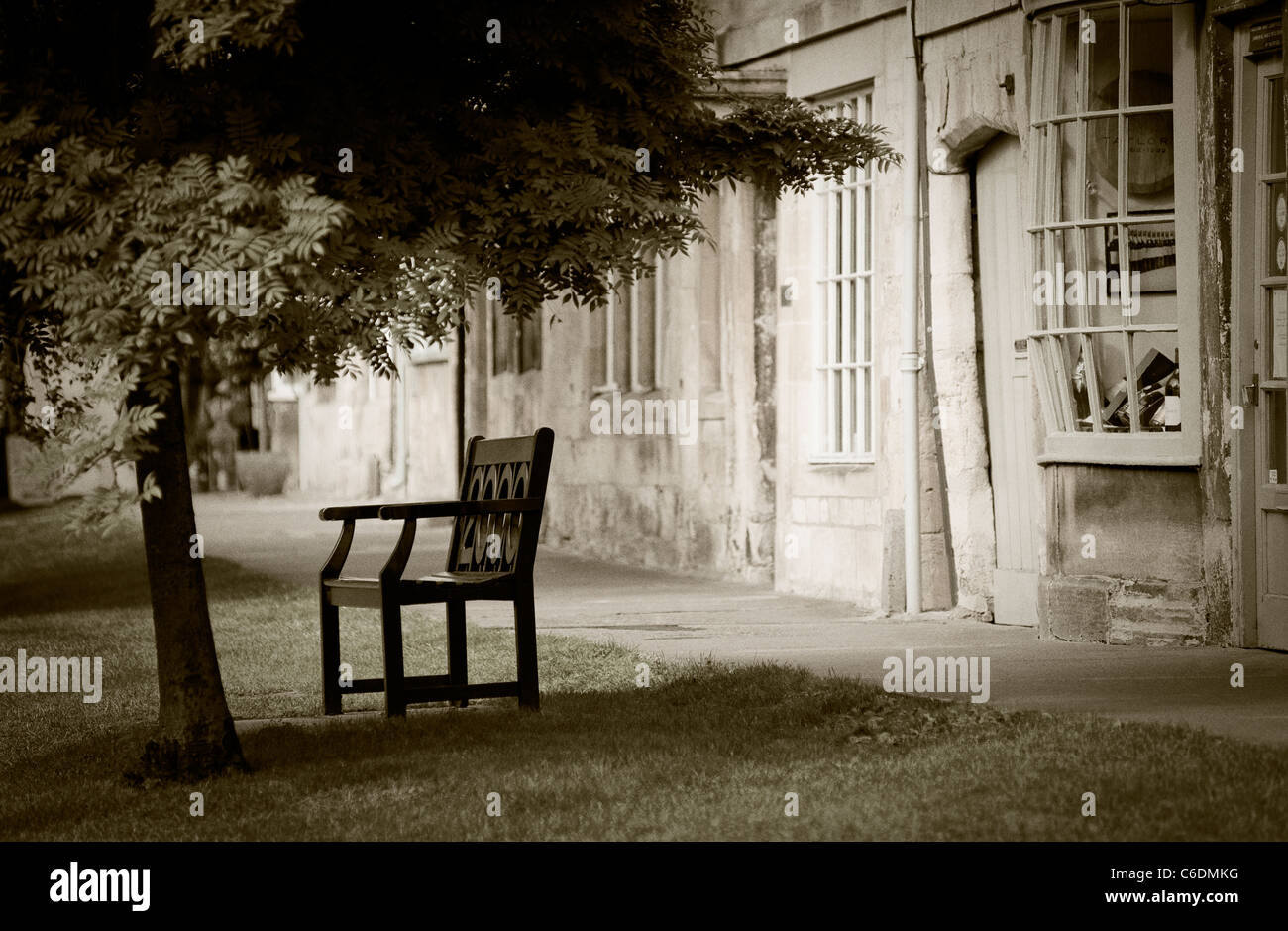 A dreamy image of an old English street scene featuring an old fashioned shop and a bench shot in Chipping Camden Stock Photo