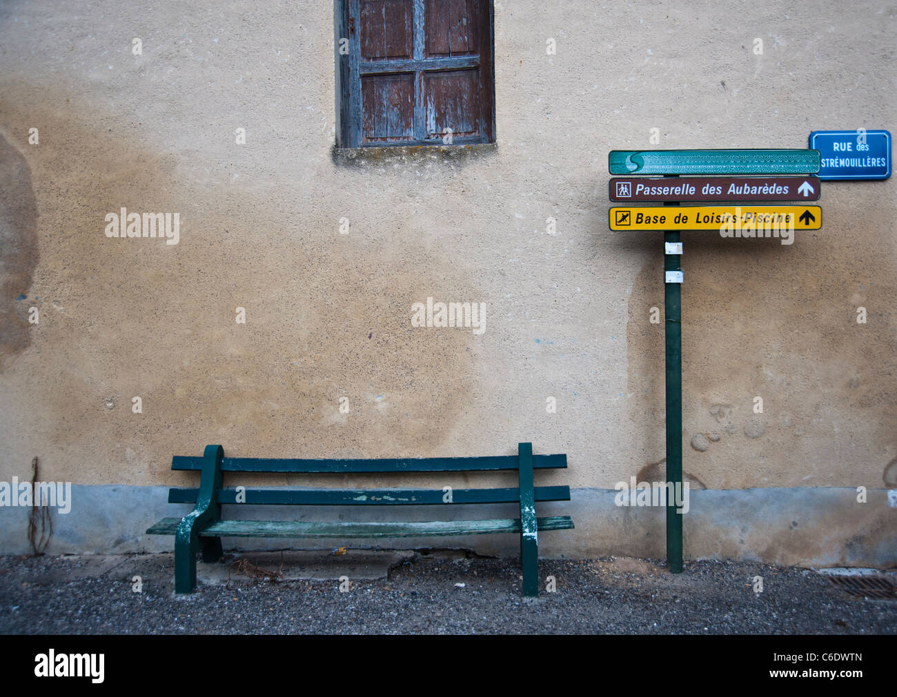 French wall with bench and signposts - natural muted colours on Beaulieu sur Dordogne Stock Photo