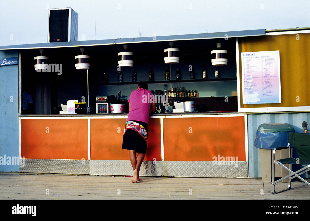 Punter waiting for the bartender to serve in King Kamehameha Beach Club at Hafeninsel in Offenbach in Germany. - Stock Image