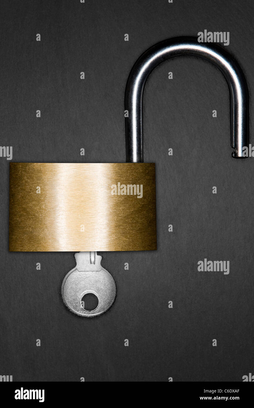 Open padlock and key on a dark slate background - Stock Image