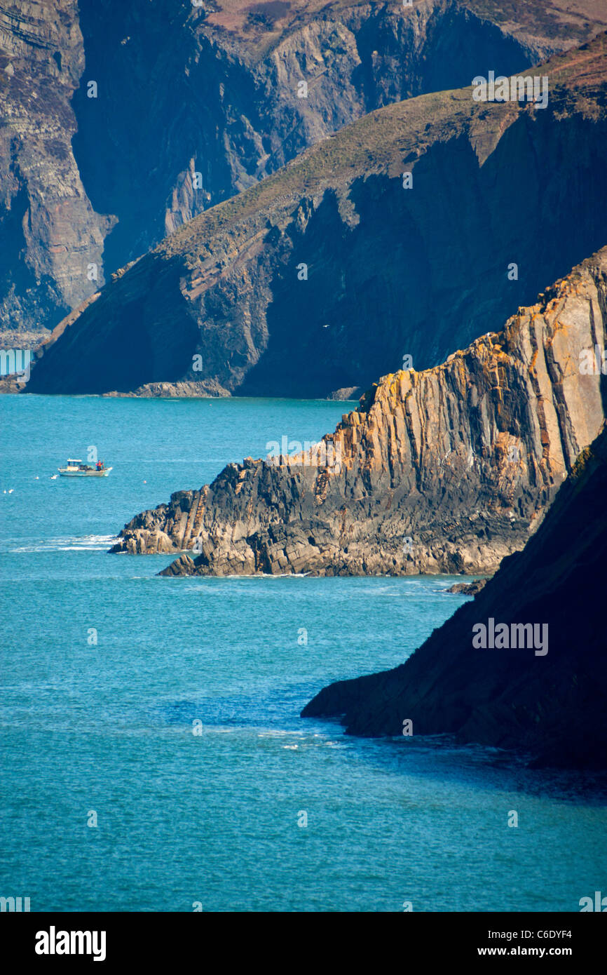 Cliffs on coast looking from Ceibwr Bay to Pen yr Afr with fishing boat in cove Pembrokeshire West Wales UK - Stock Image