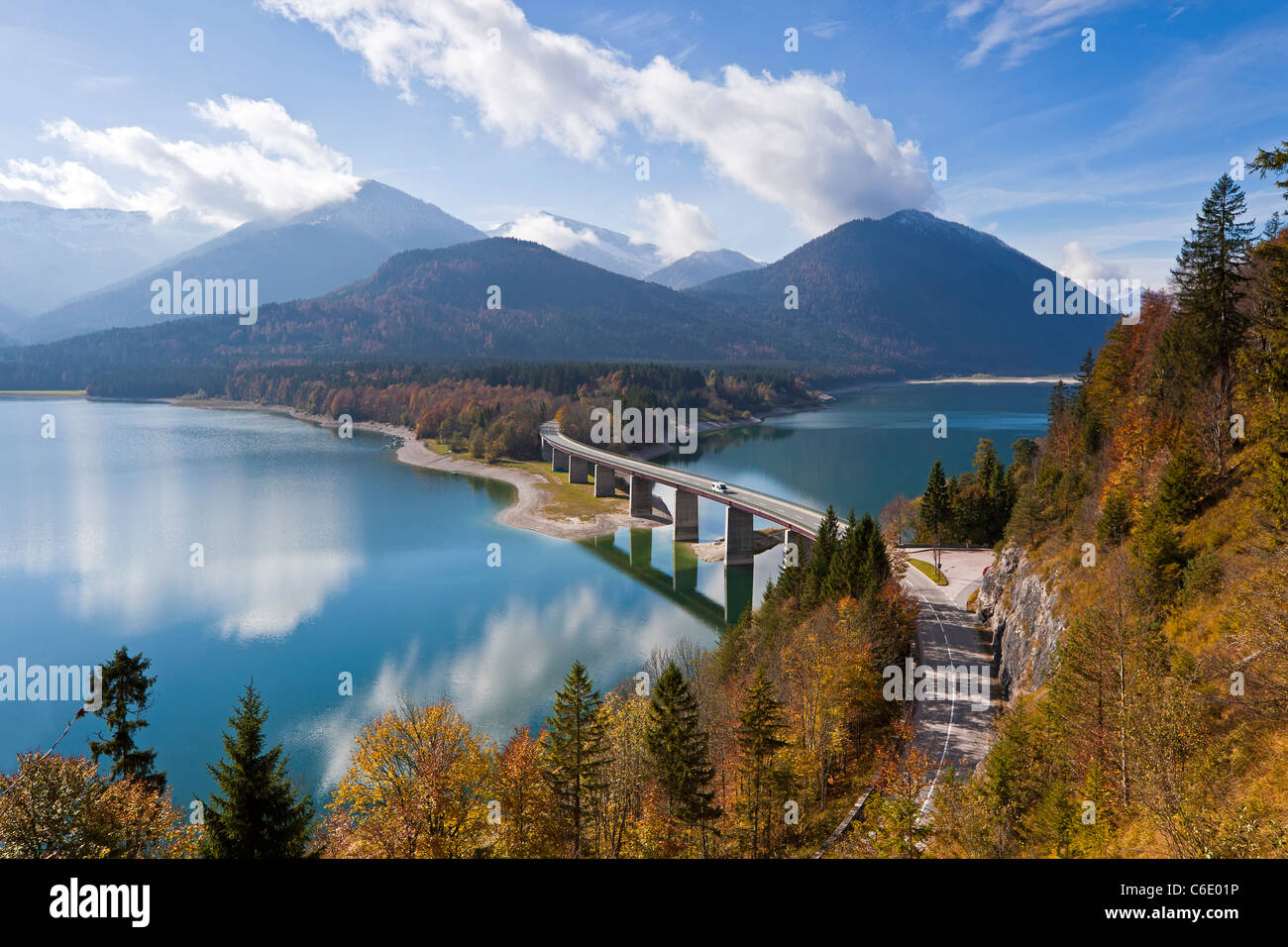 Reflections of a road bridge over Lake Sylvenstein, with mountains in the background, in Bavaria, Germany - Stock Image