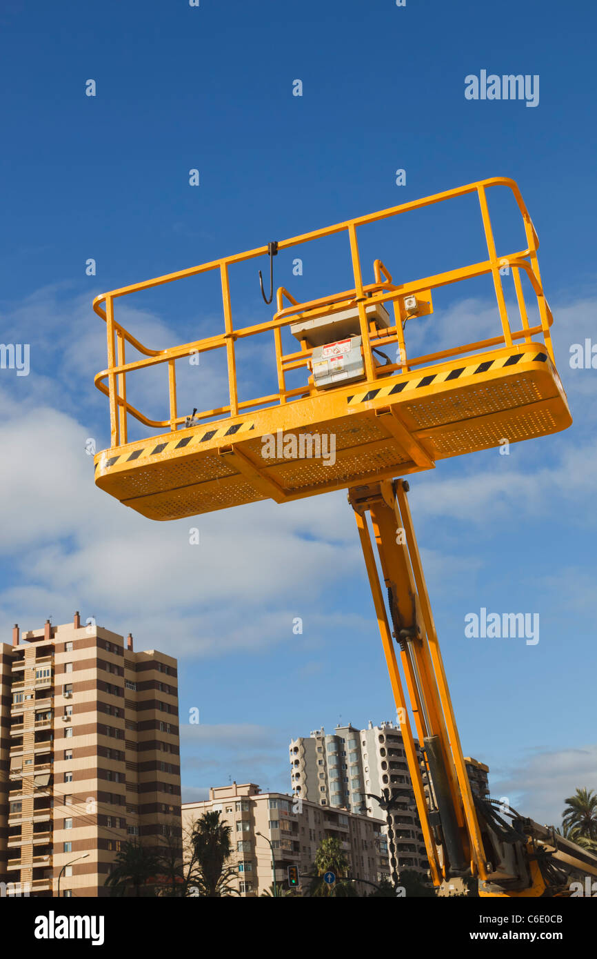 Empty cherry picker cradle against sky in urban cityscape. Malaga, Malaga Province, Spain. - Stock Image