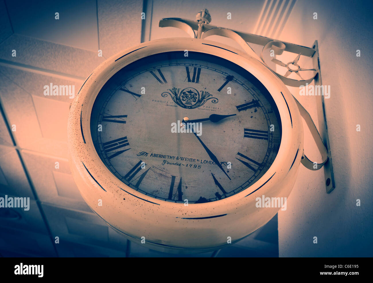 Old clock with Roman numerals on wall. - Stock Image
