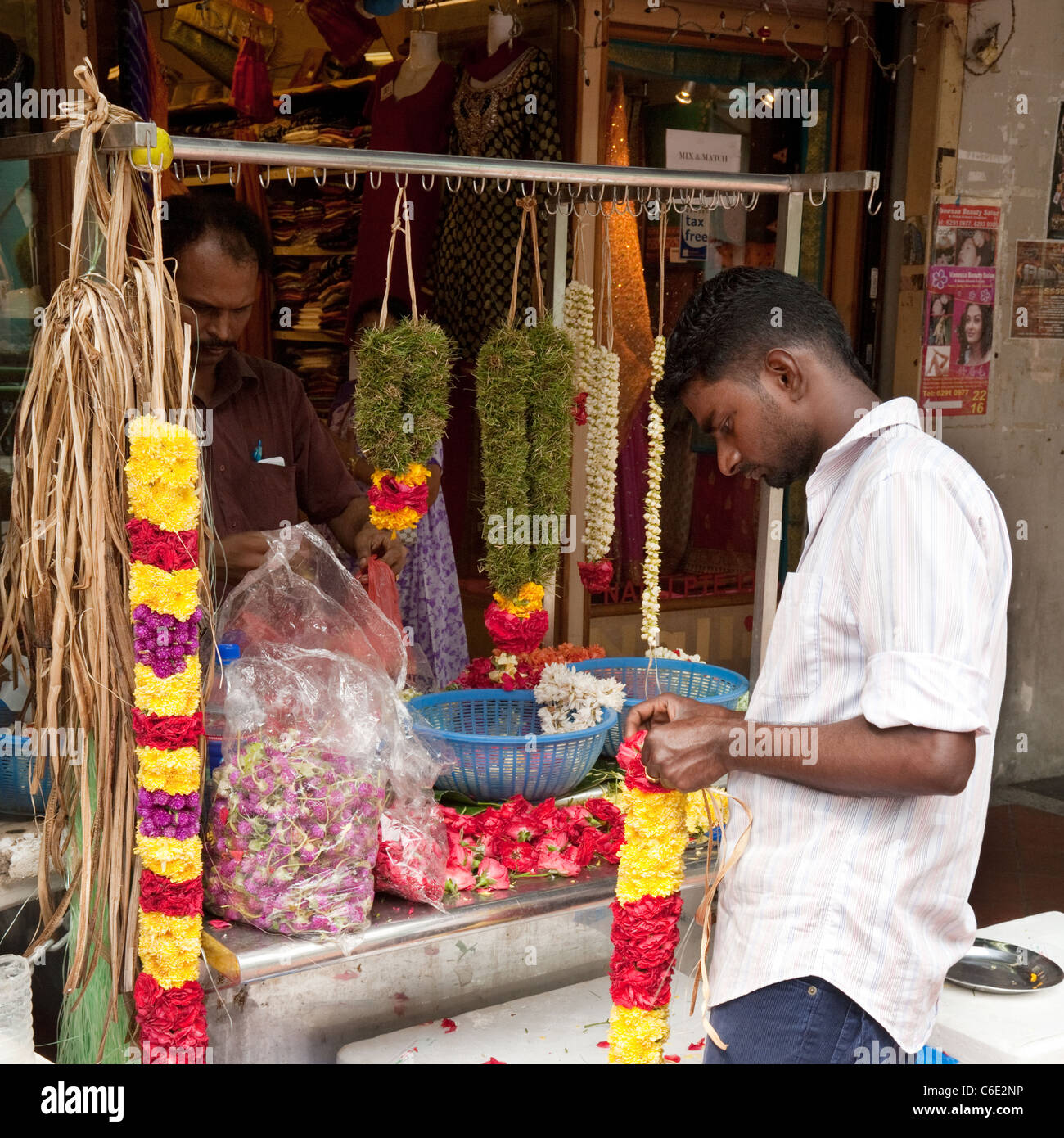 A shopkeeper making flower garlands, Little India, Singapore Asia - Stock Image