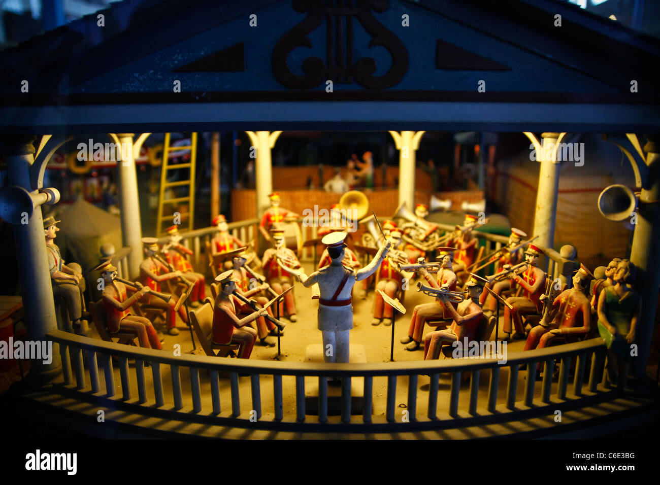 Antique animated wooden band in a bandstand playing music at night. - Stock Image