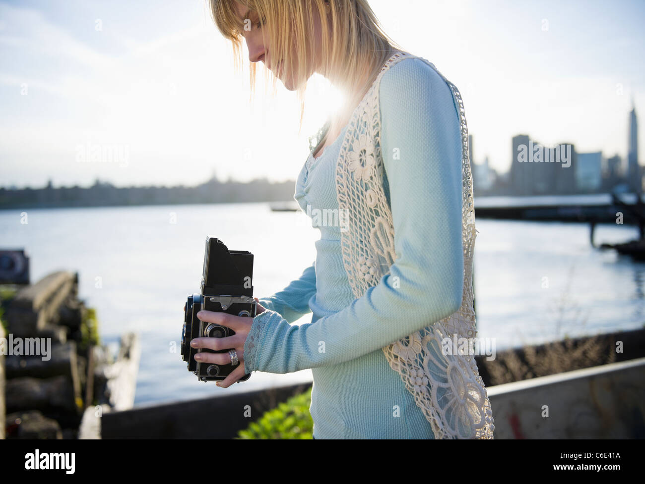 USA, Brooklyn, Williamsburg, Woman using vintage camera - Stock Image
