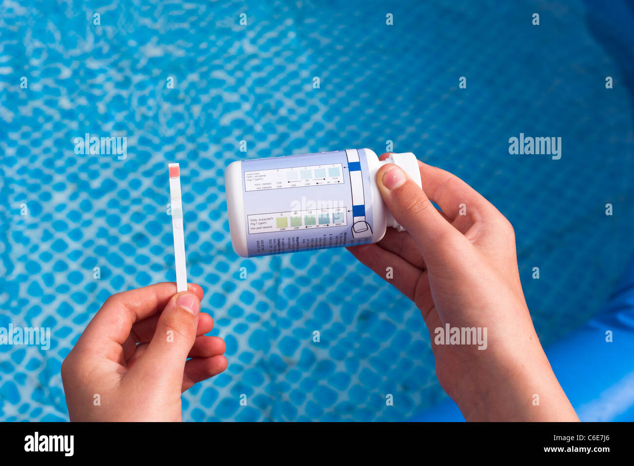 Testing a swimming pool with a testing stick dip test for alkalinity , chlorine and PH levels - Stock Image