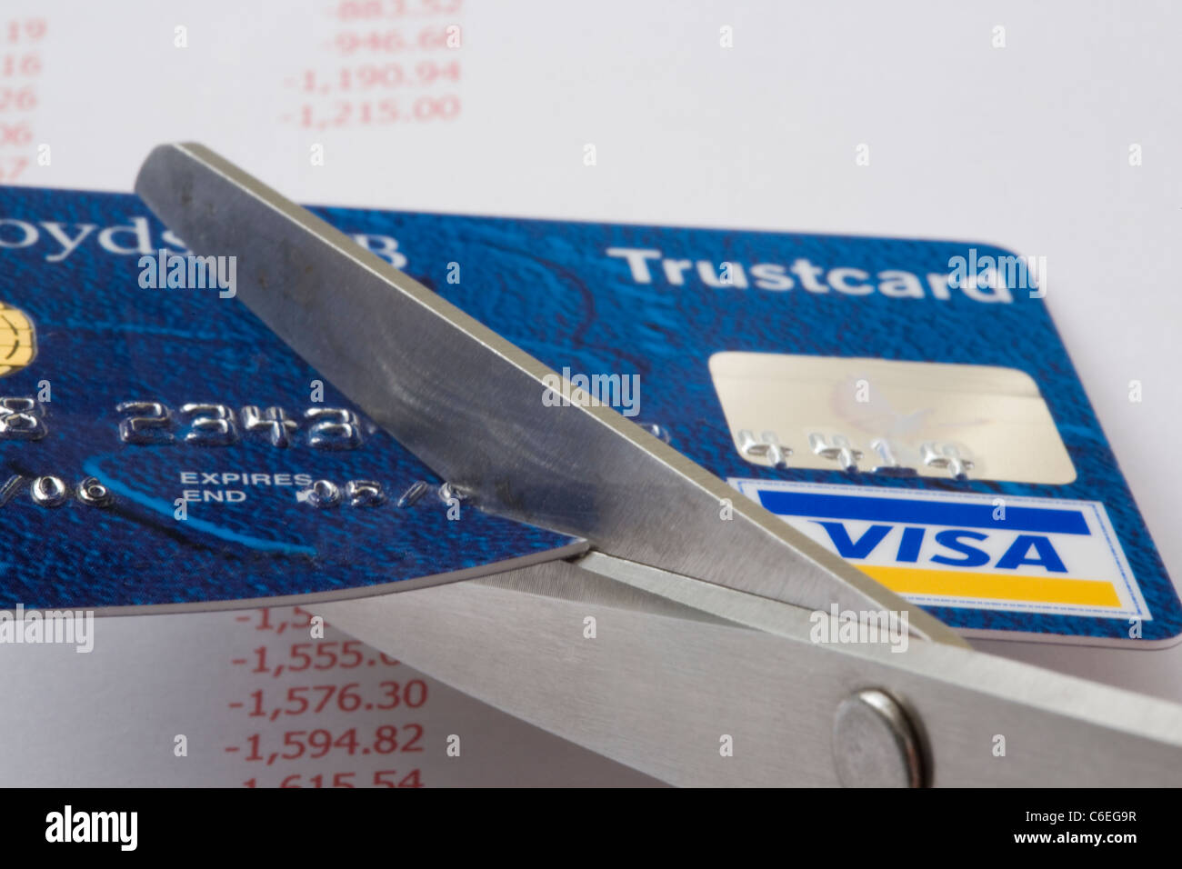 Pair of scissors cutting a Visa credit card in close up above an accounts sheet showing debts in red. England, UK, - Stock Image