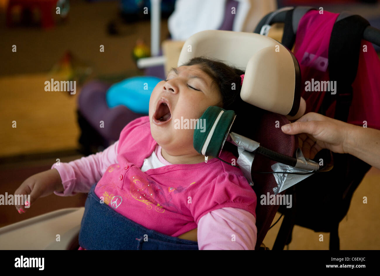 Seven year old deaf blind child vocalizing during a speech therapy session in school. - Stock Image