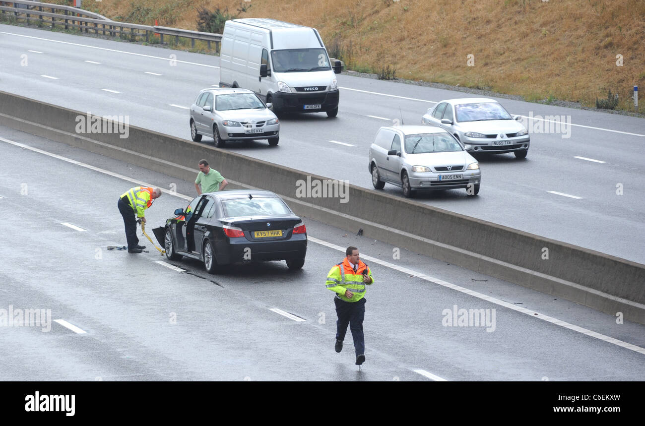 HIGHWAYS AGENCY TRAFFIC OFFICERS  ATTENDS TO A  STRANDED MOTORIST  IN THE FAST LANE OF THE M6 MOTORWAY  FOLLOWING - Stock Image