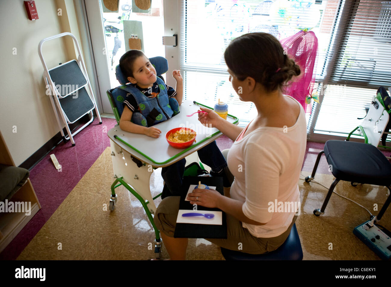 Speech therapist working with young boy on making a request for more food using sign language. - Stock Image