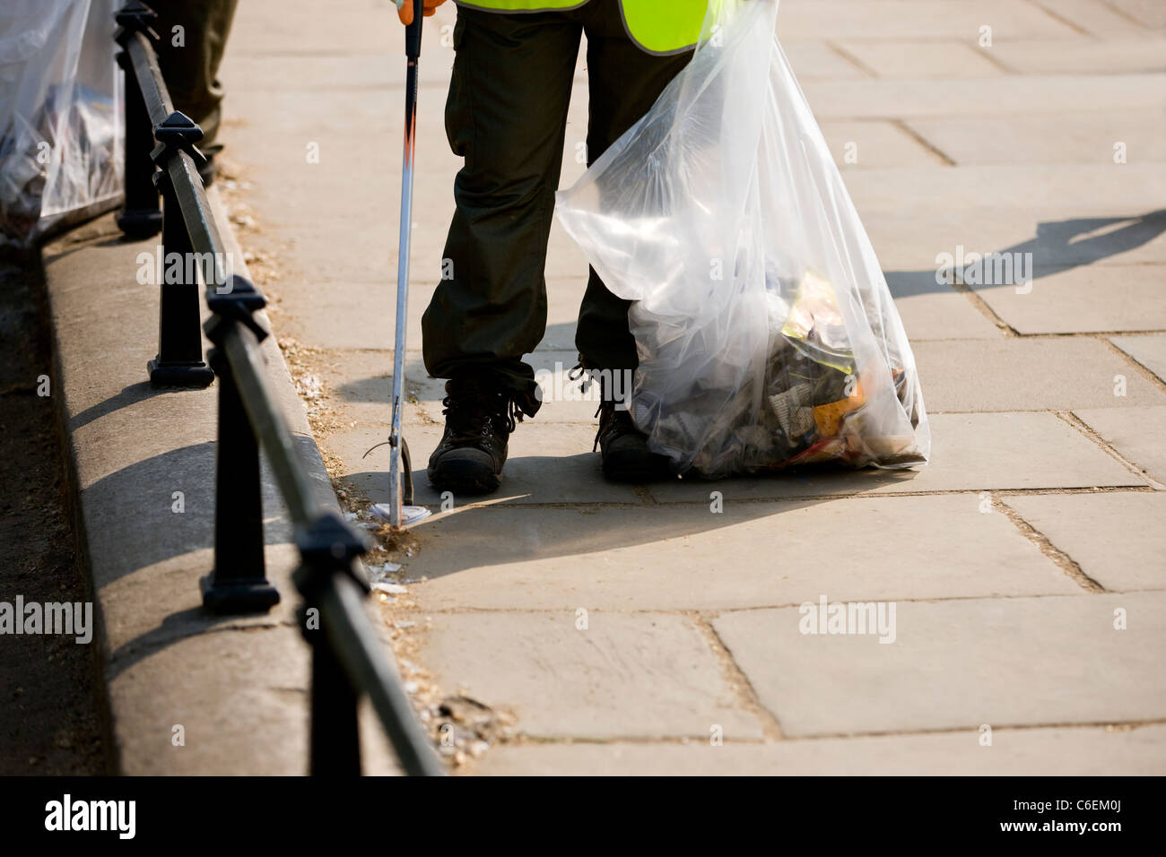 A man collecting rubbish from the street - Stock Image
