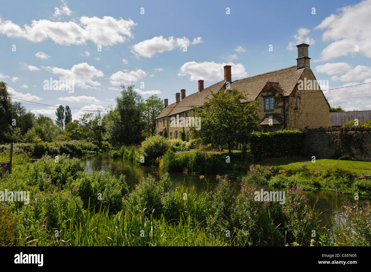 Houses beside the River Coln in the Gloucestershire village of Fairford - Stock Image