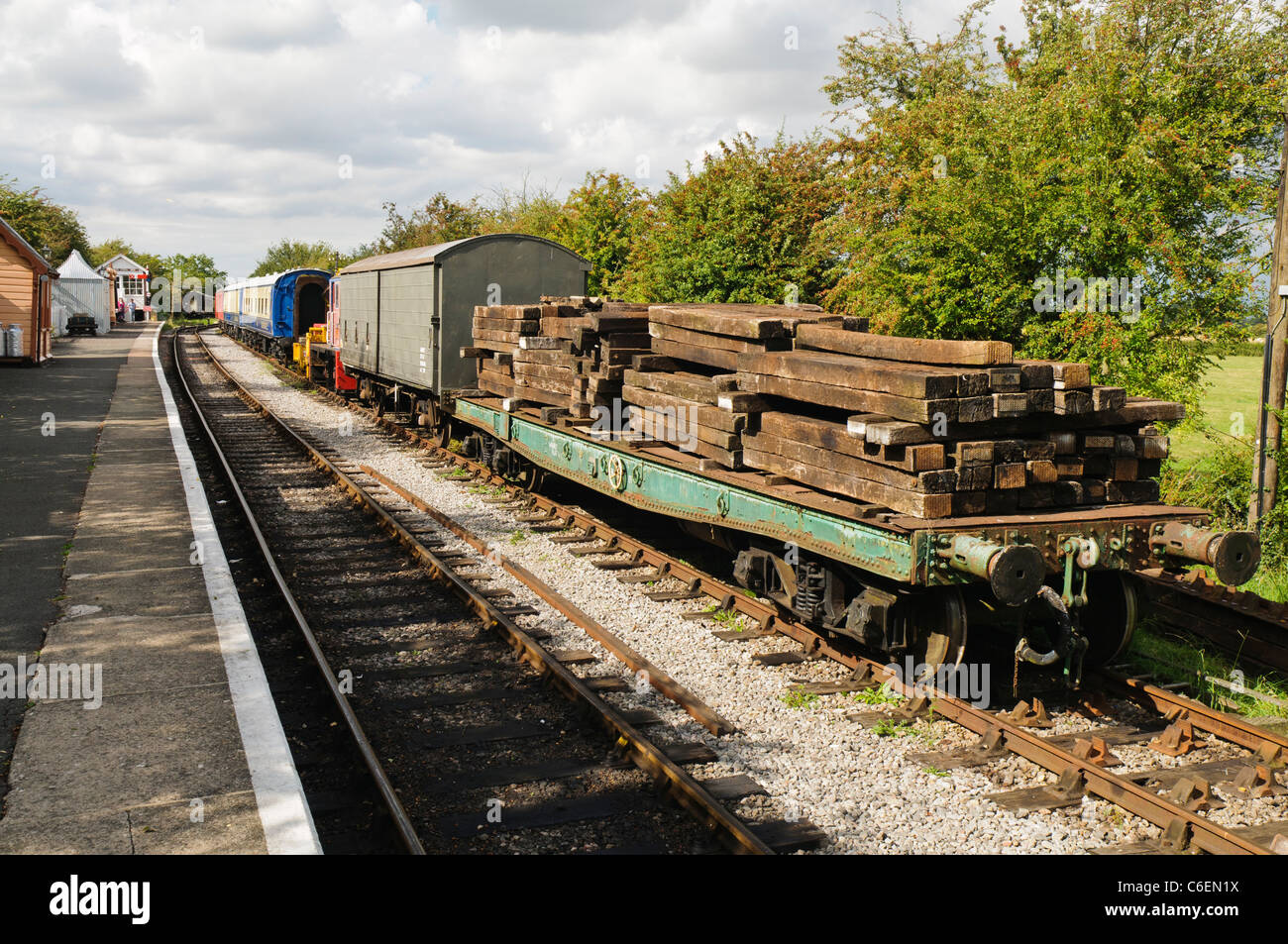 Old fashioned freight carriages including one carrying sleepers at the platform of a train station - Stock Image