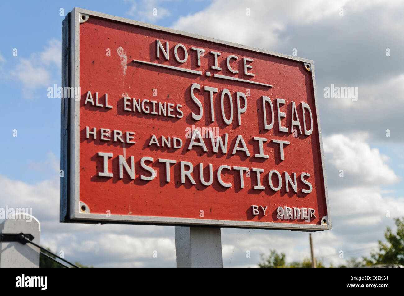 Sign on a railway instructing drivers to stop dead and await instructions - Stock Image