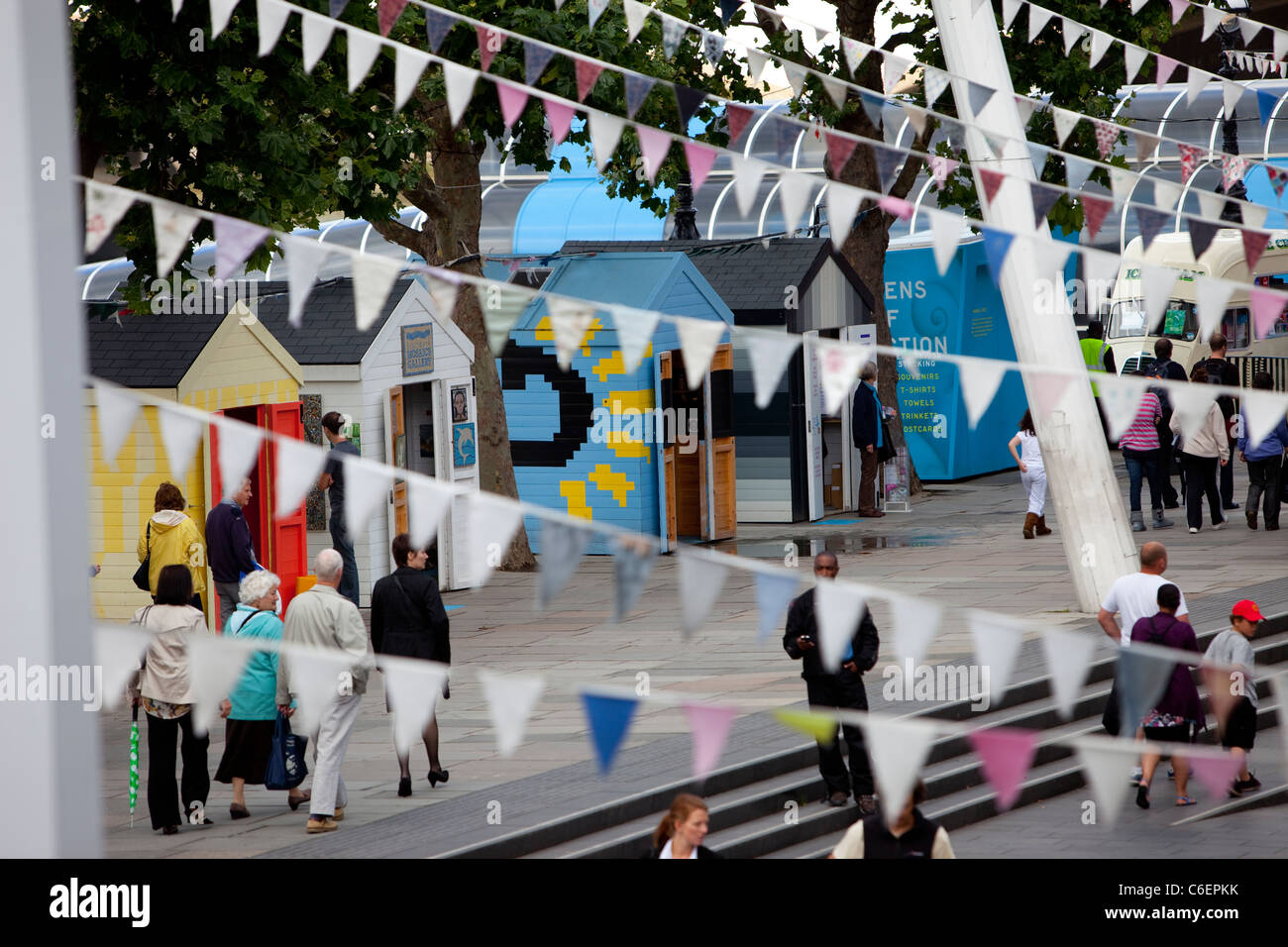 Tourists wander amongst the art installations and bunting on the Southbank, London. - Stock Image