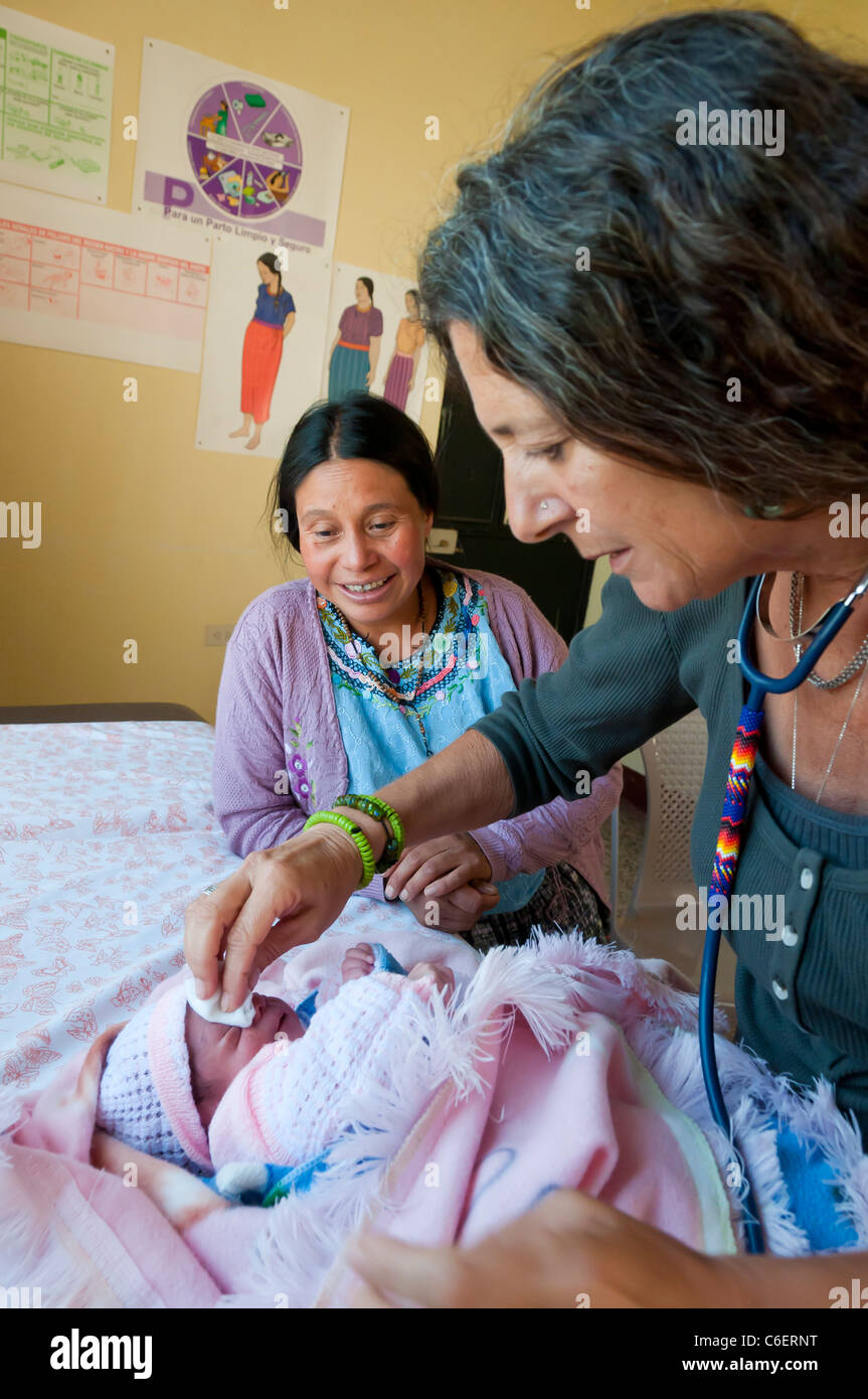 Foreign medical specialist from an NGO looking at a Mayan baby in a free health clinic in the Atitlan region Guatemala - Stock Image