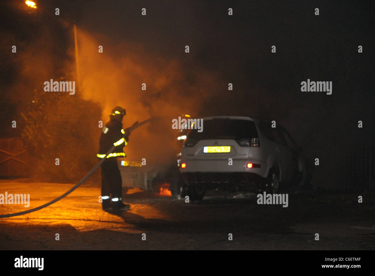 Firefighters extinguish flames in a car after an accident - Stock Image