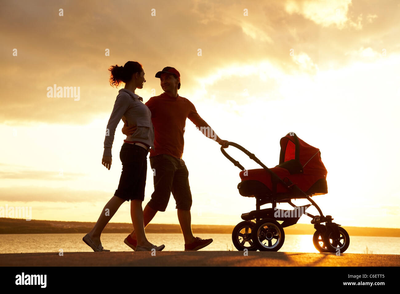 Silhouettes of happy parents walking with stroller on the seacoast - Stock Image