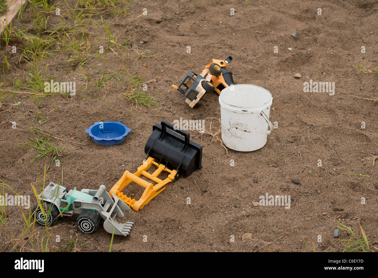 Toys spread out in a sandbox - Stock Image