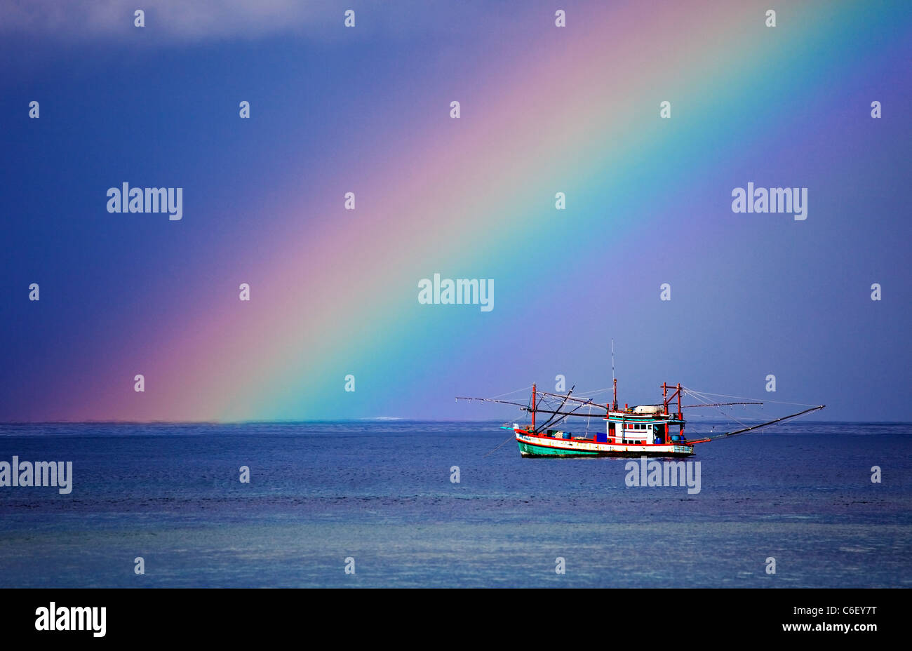 A Rainbow and Fishing Boat in Thailand - Stock Image