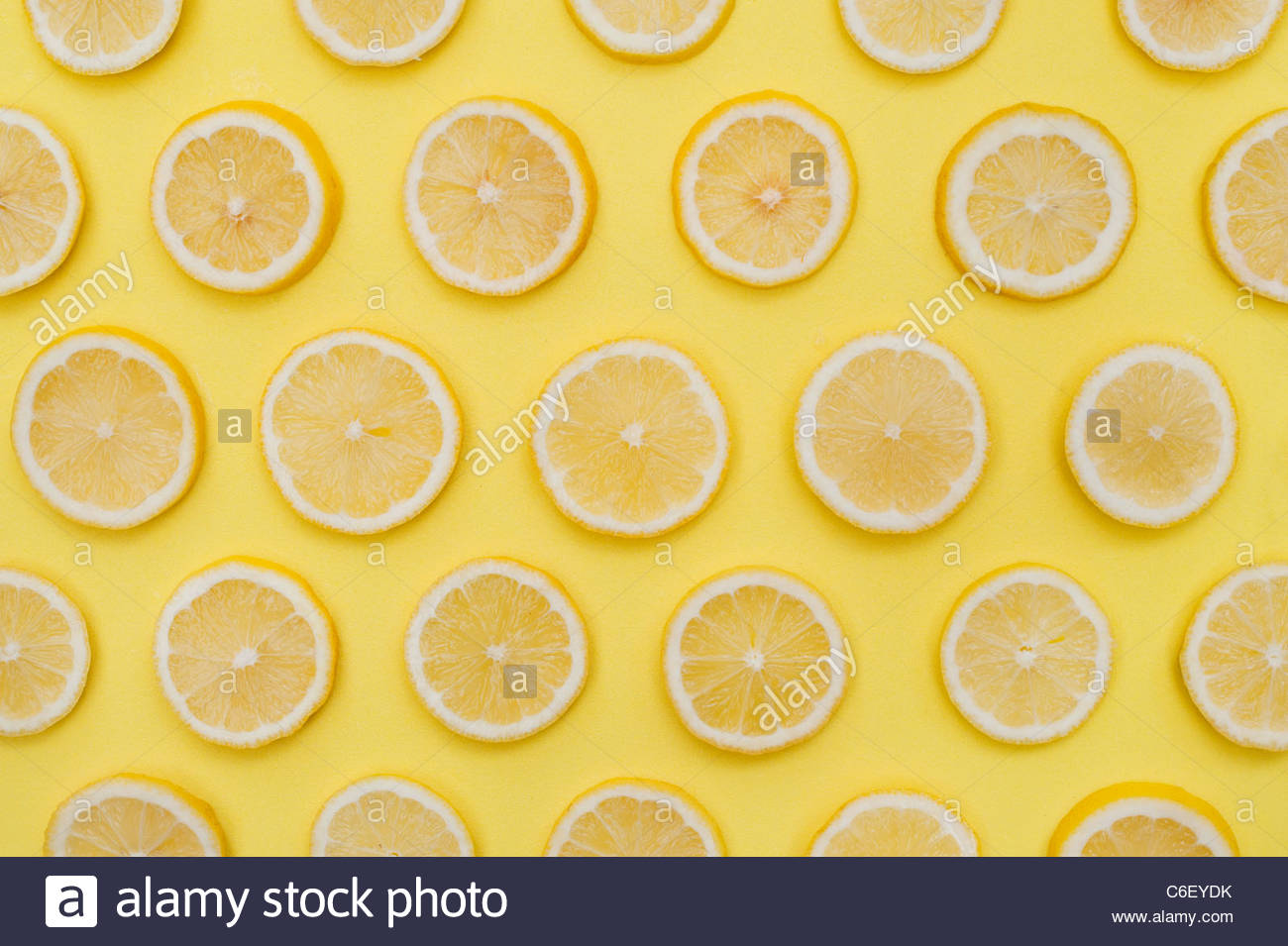 Citrus x Limon . Lemon fruit slices on yellow background . Food pattern - Stock Image