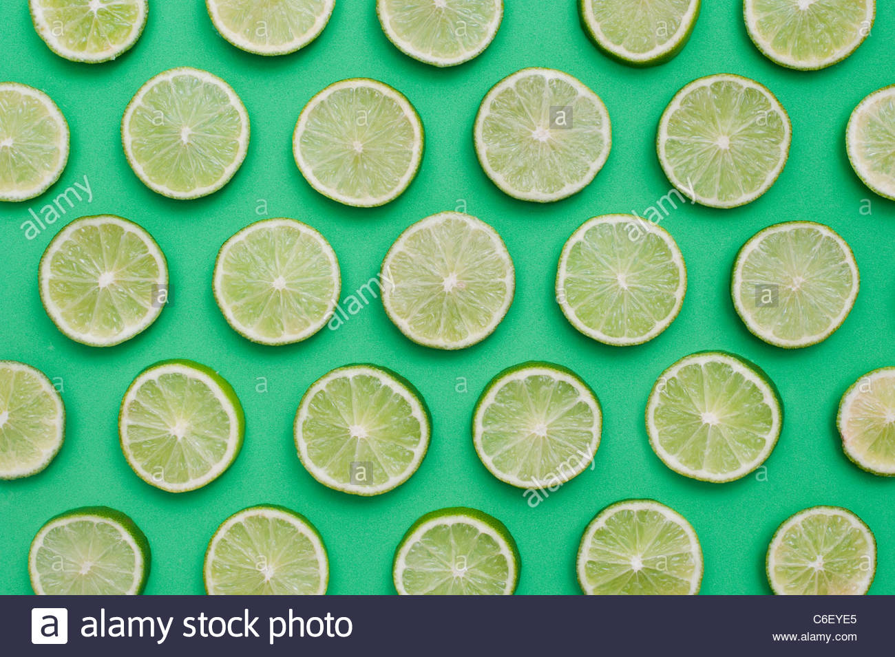 Citrus x​ sinensis. Lime fruit slices on green background . Food pattern - Stock Image