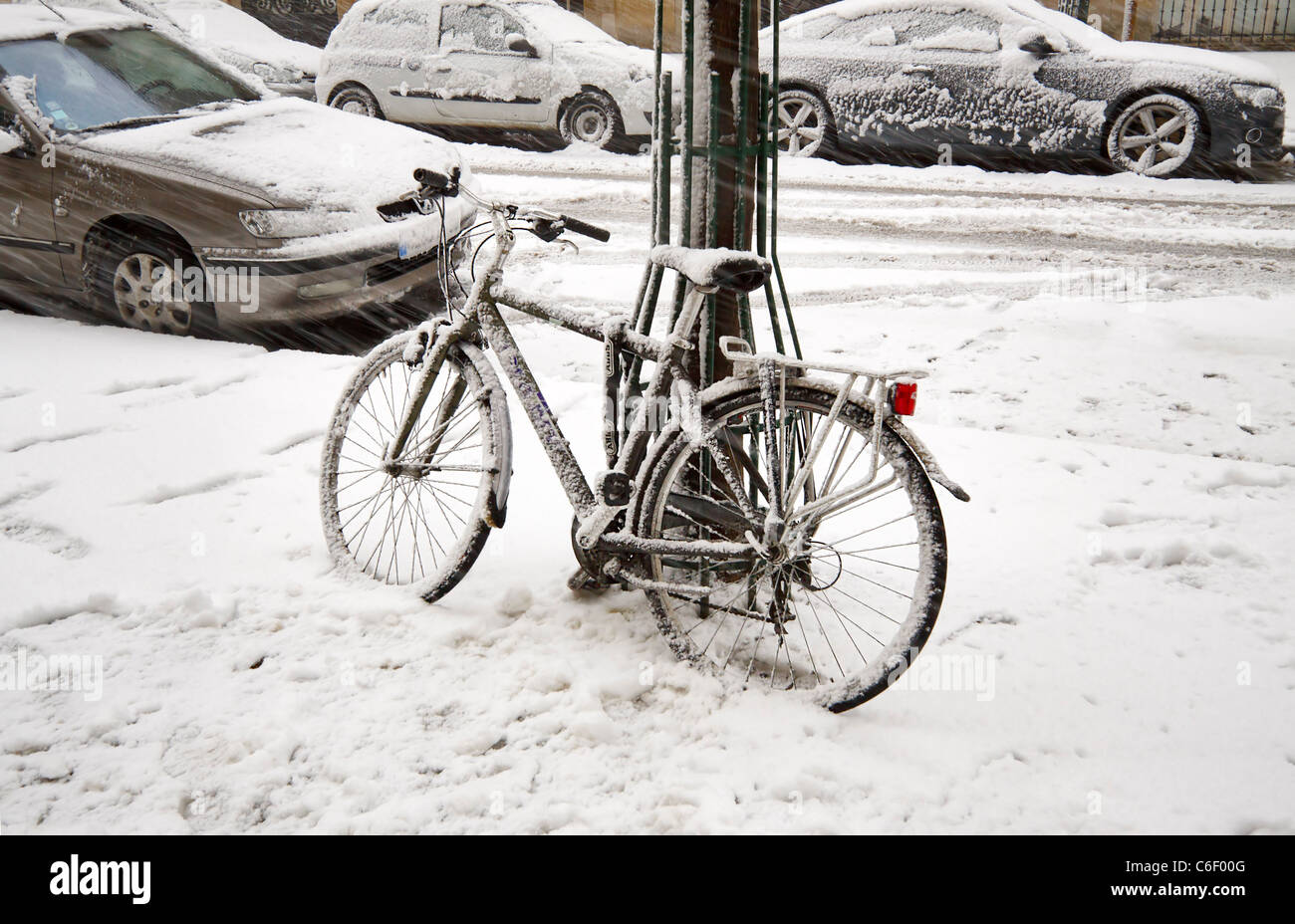 A bicycle and parked cars covered in snow during an early winter snowstorm in Paris, France ROYALTY FREE - Stock Image