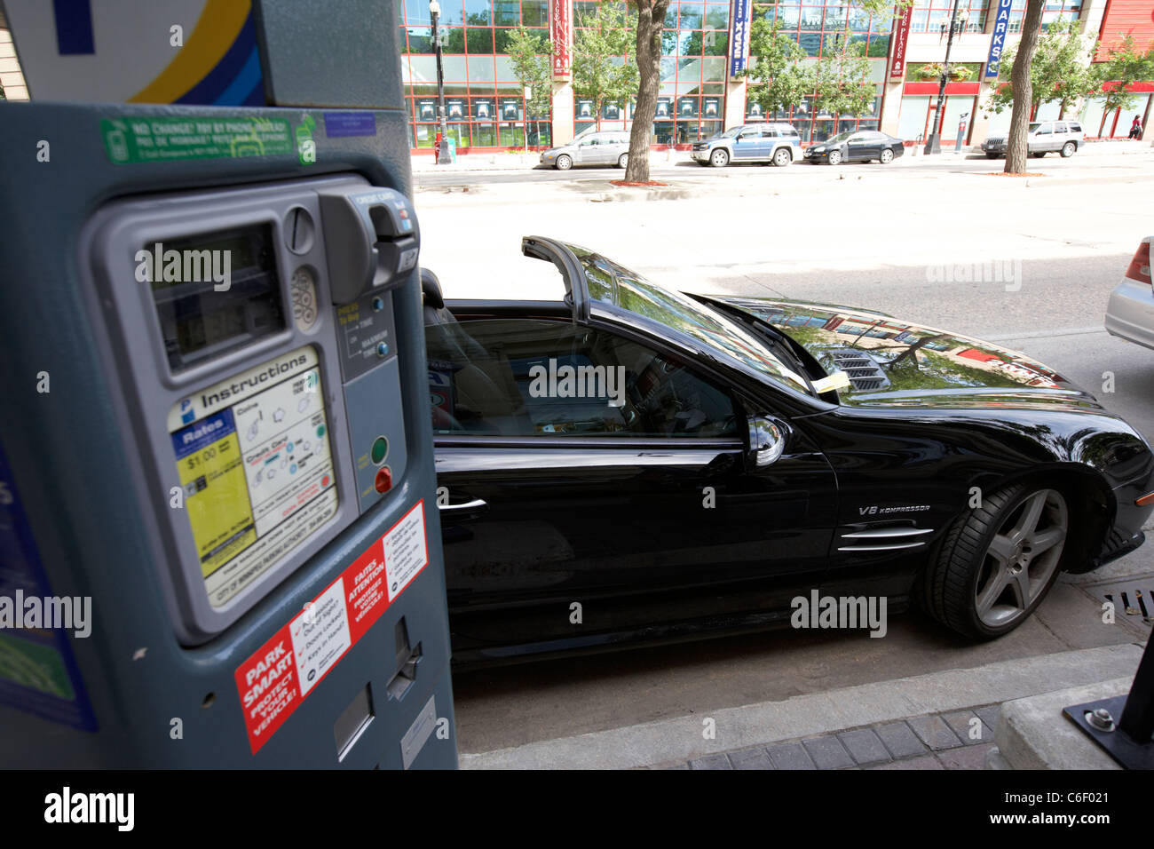 parking ticket on luxury mercedes car illegally parked on street in downtown winnipeg manitoba canada - Stock Image