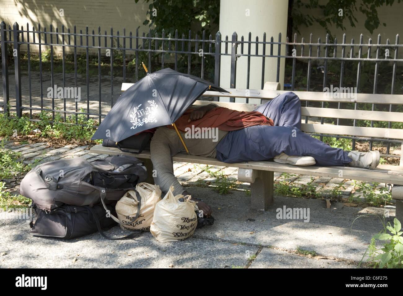 homeless; homelessness; man; sleeping; bench; alone; outside; belongings; Brooklyn; New York City; NYC; USA; America - Stock Image
