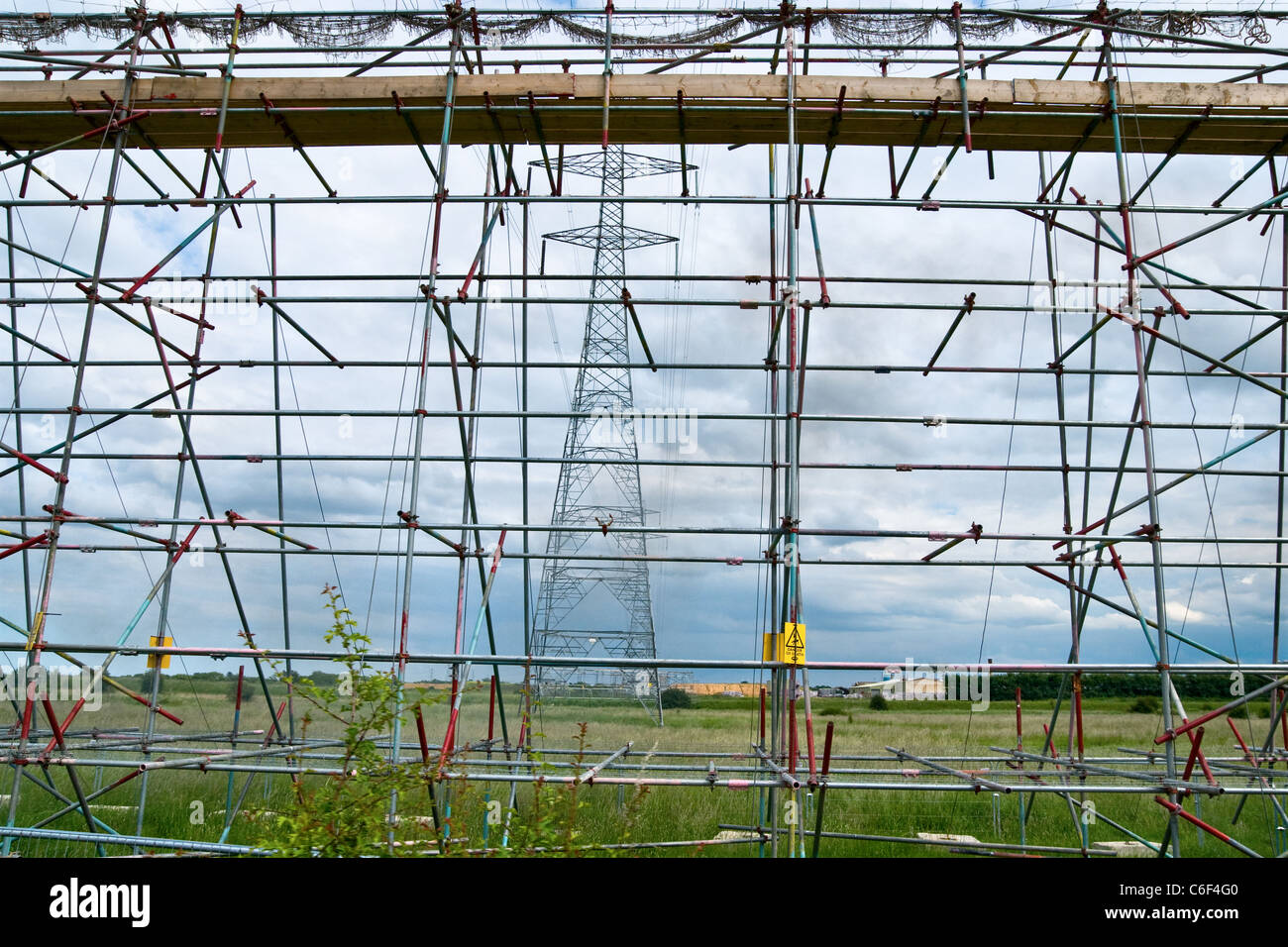 Scaffolding to protect the public from falling wires and the electric company that is renewing the overhead cables - Stock Image
