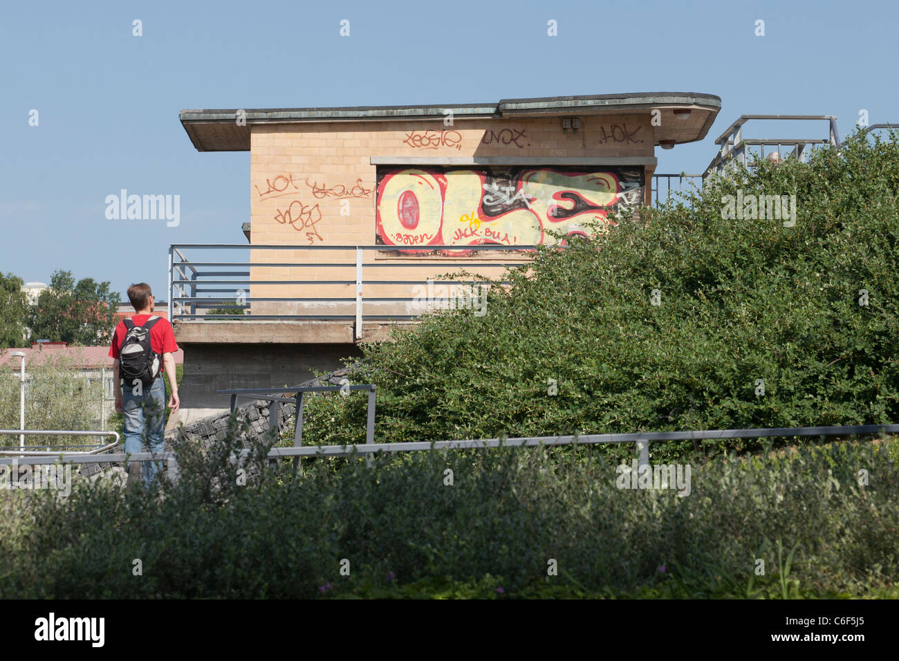 A man walking  towards the wall which is smudged with graffiti and mess. - Stock Image