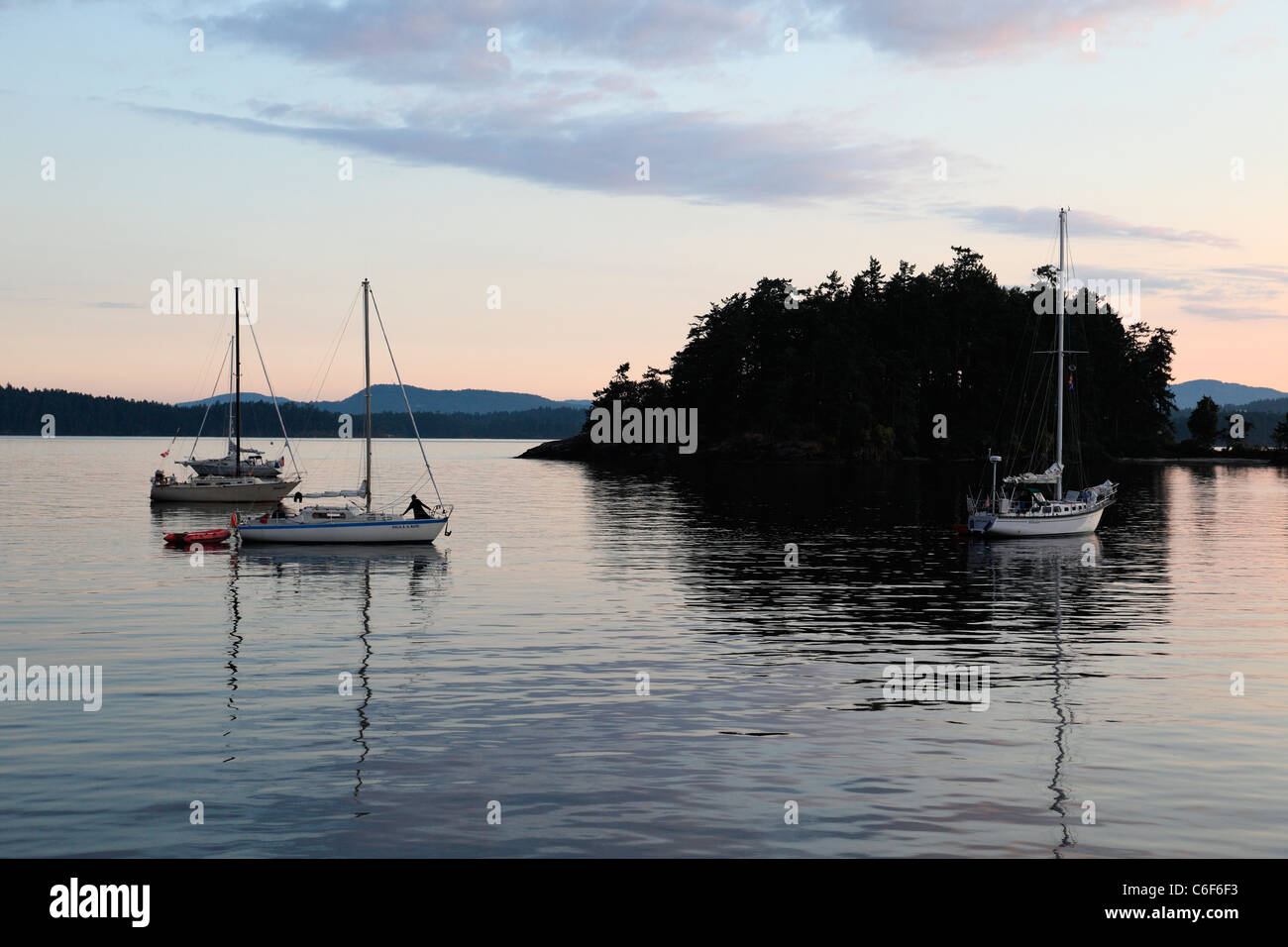 Sailboats anchored in Haro strait near portland island at sunset - Stock Image