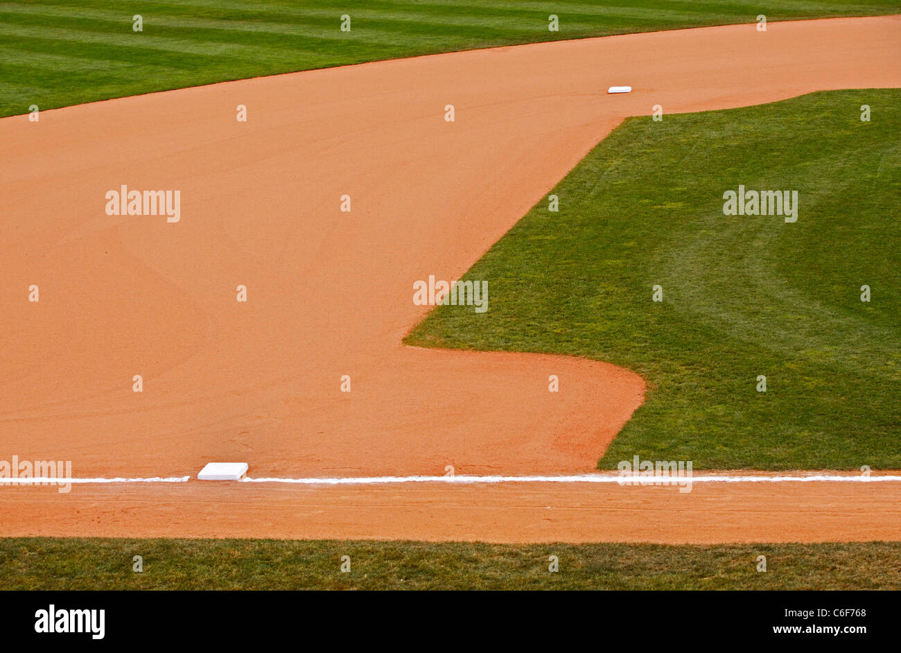 A portion of an baseball park's dirt and grass infield showing second and third bases. - Stock Image