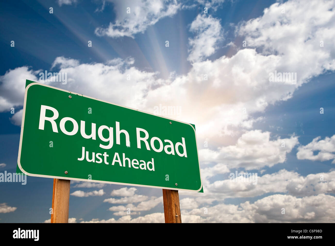 Rough Road, Just Ahead Green Road Sign Over Dramatic Sky, Clouds and Sunburst. Stock Photo