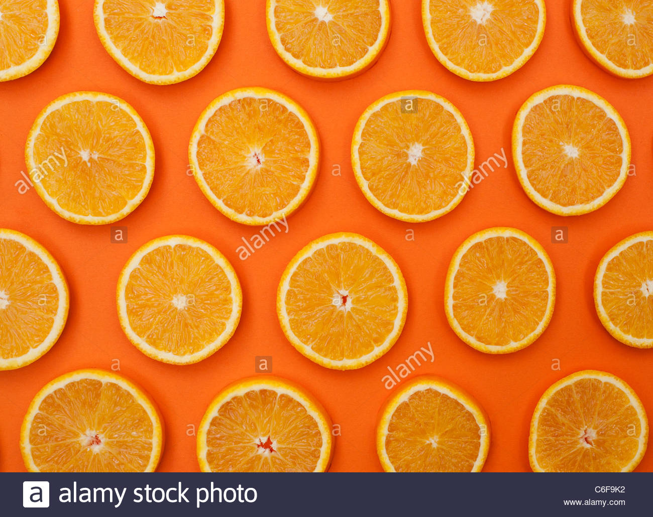 Citrus x sinensis. Orange fruit slices on orange background . Food pattern - Stock Image