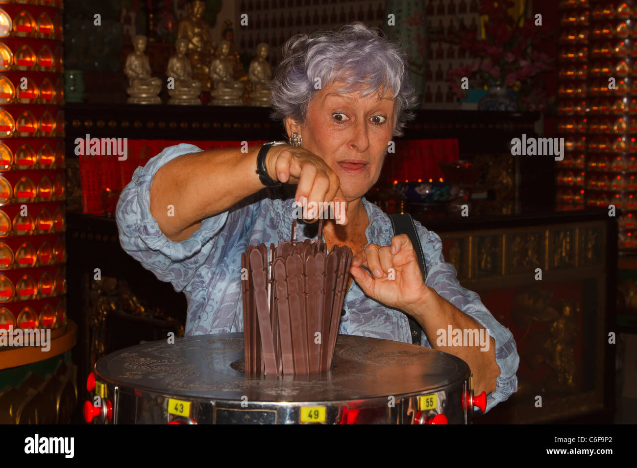 An elderly woman using the Kau Cim, fortune telling sticks in the Chinese Thean Hou Temple, Kuala Lumpur, Malaysia. - Stock Image