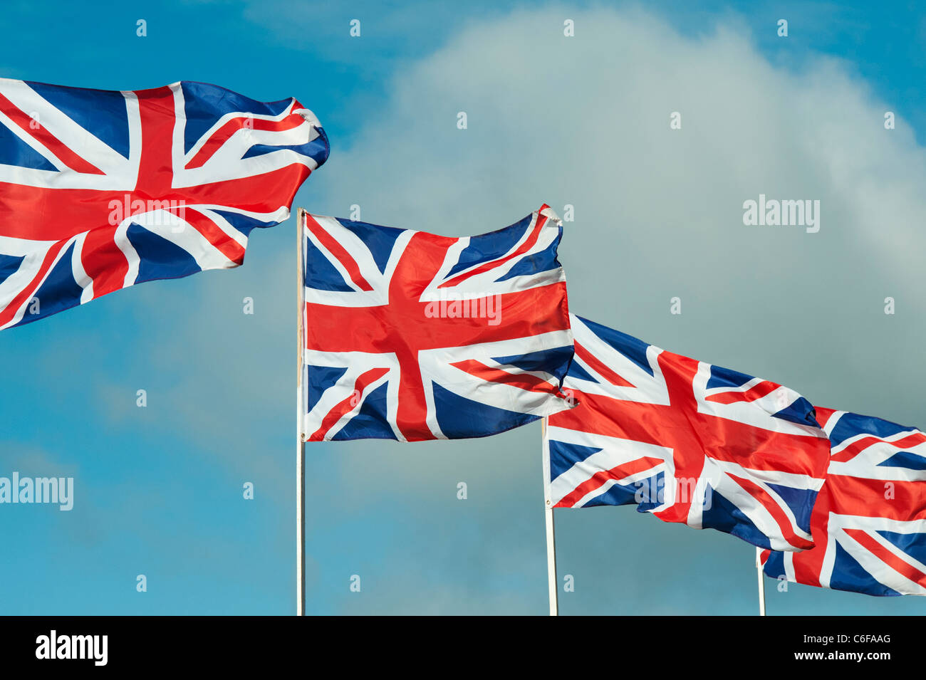 Four Union Jack flags flapping in the wind against a blue sky - Stock Image