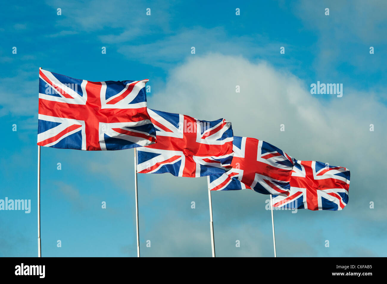 Four Union Jack flags flapping in the wind against a blue sky Stock Photo