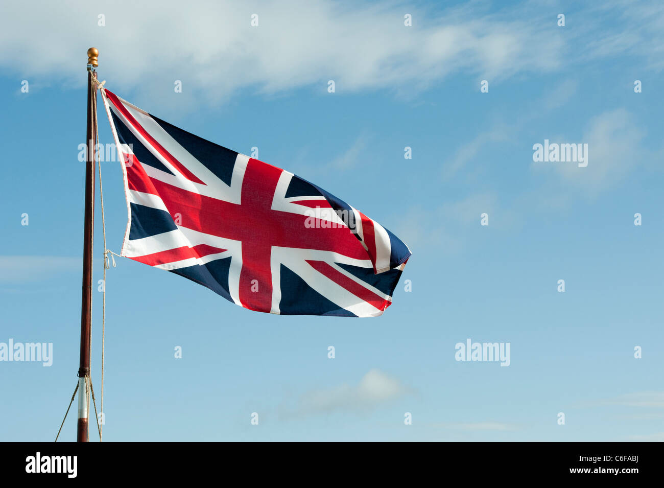 Union Jack flag flapping in the wind against a blue sky - Stock Image