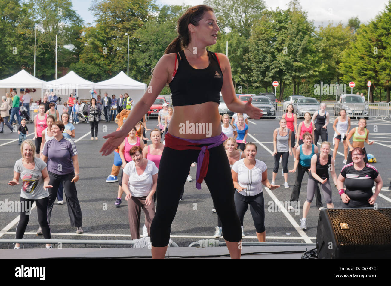 Large number of ladies take part in an outdoor Zumba class - Stock Image