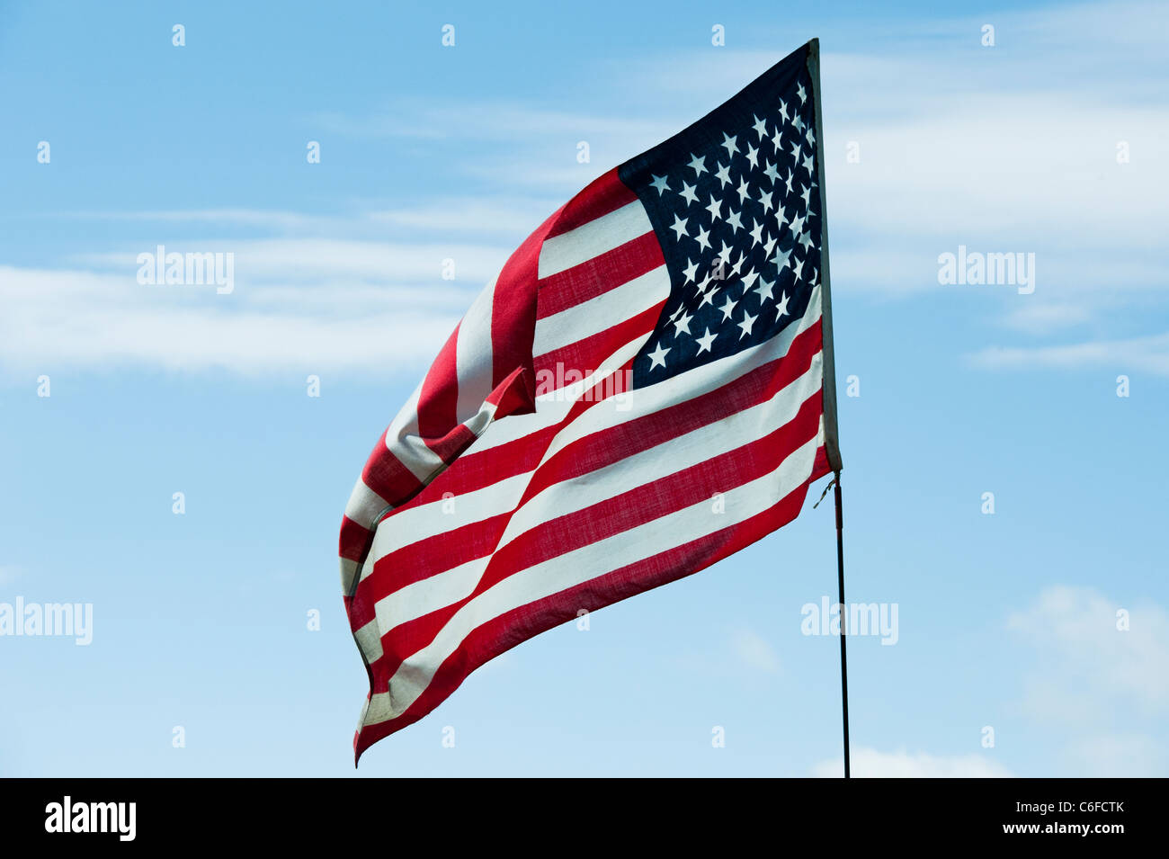 American flag on a flagpole blowing in the wind - Stock Image