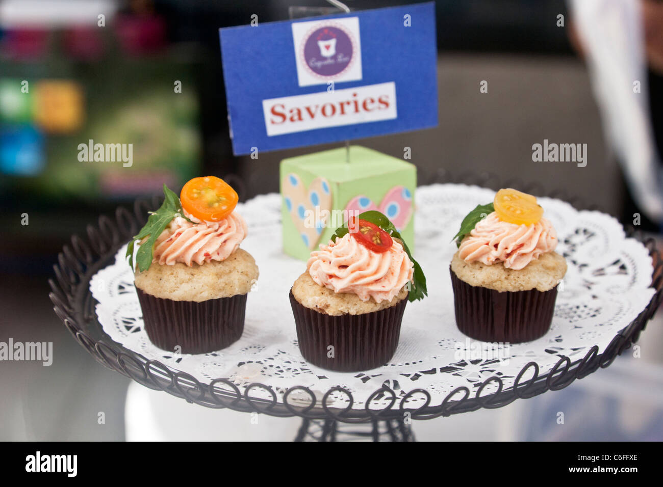 mouth watering display of three one of a kind mini cupcakes topped with strawberry icing & individual slices of Stock Photo